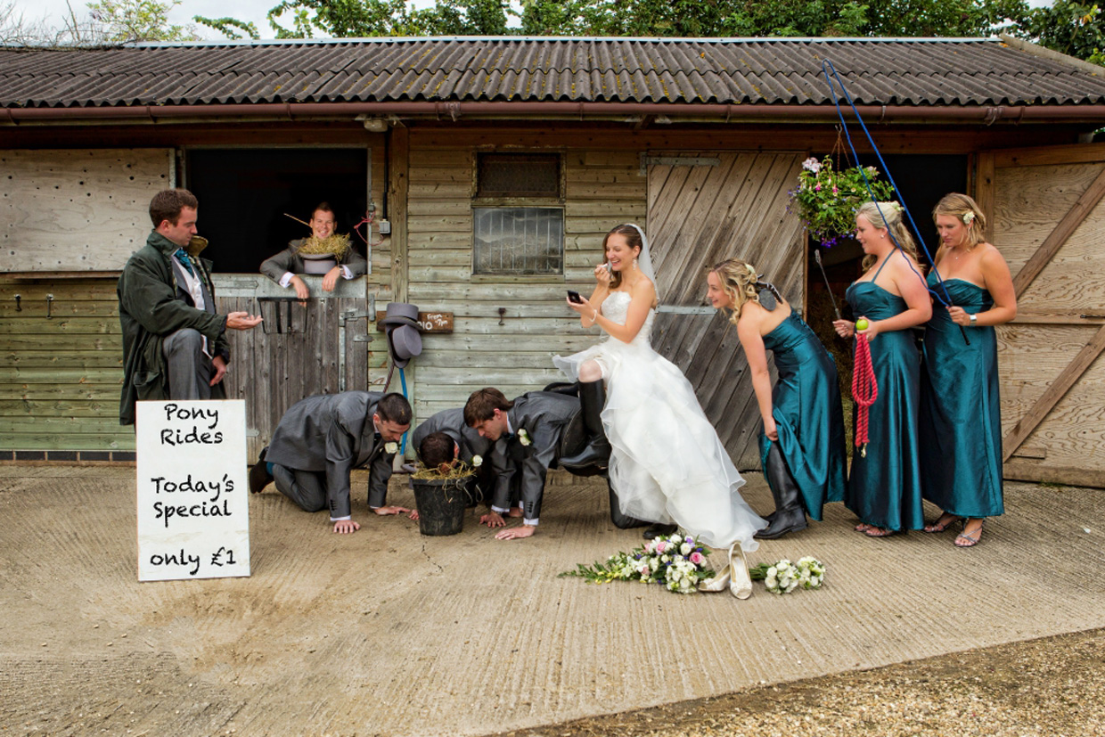 Creative wedding party photography. Groom and groomsmen pretending to be ponies and give pony rides