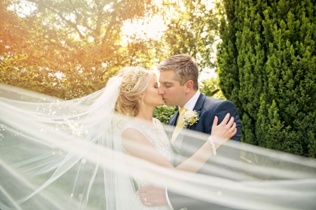 Bride kissing groom, bright and airy wedding photo taken through brides veil in the gardens at Mallory court