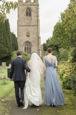 Bride , her father & maid of honour walking to church