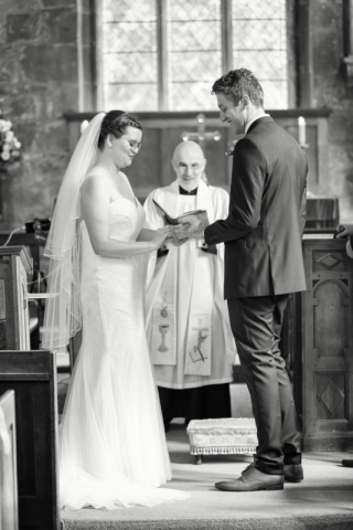 Wedding photograph of Bride and Groom exchanging rings at St Leonard's Church