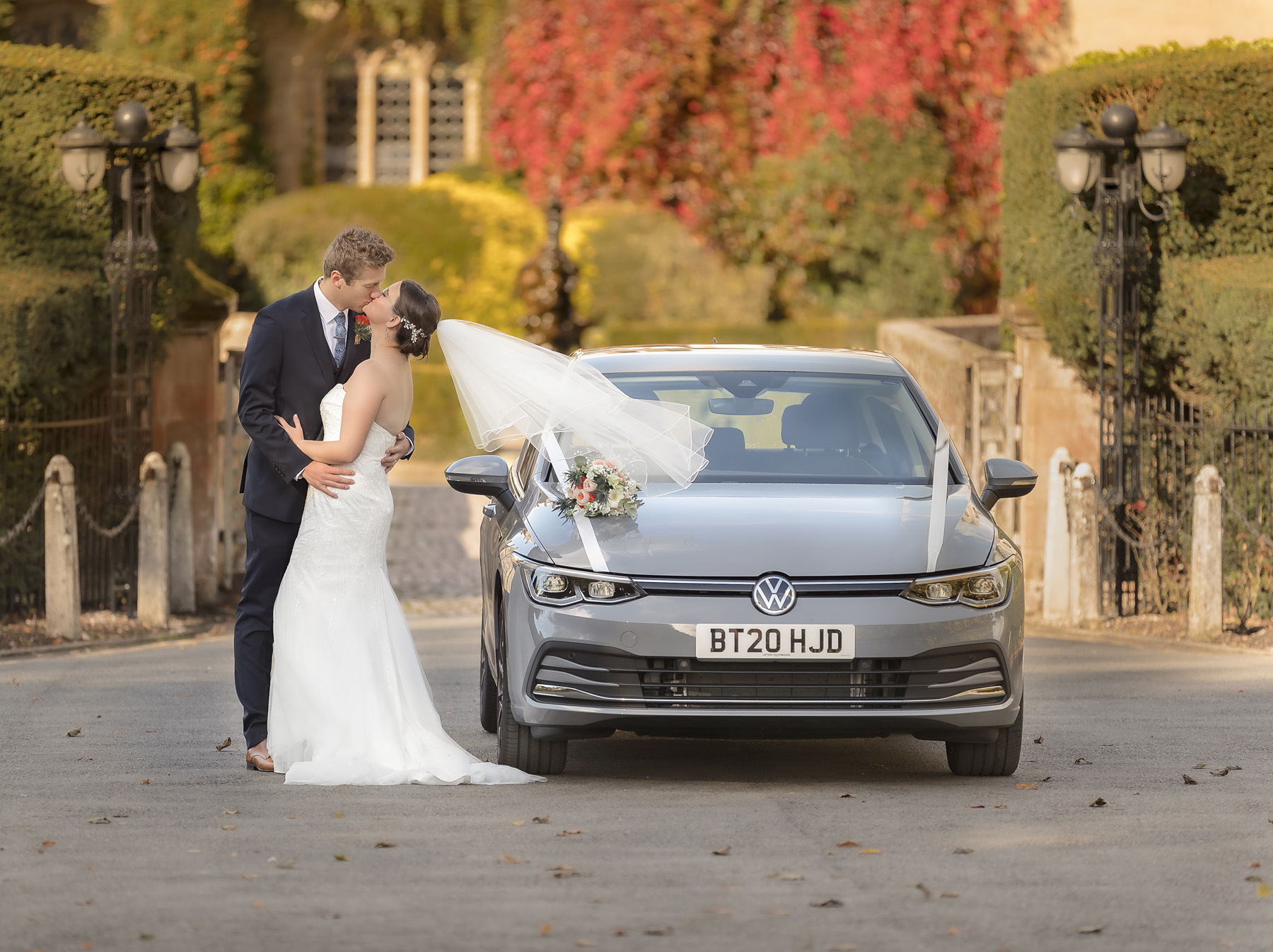 Bride and Groom romantic autumnal wedding portrait with their car in front of Coombe abbey
