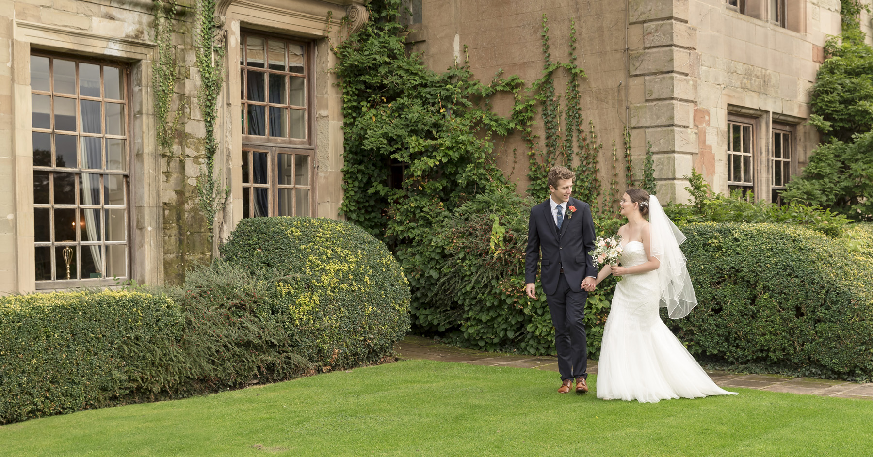 reportage wedding image of Bride and Groom walking hand in hand on the west terrace grass at Coombe Abbey