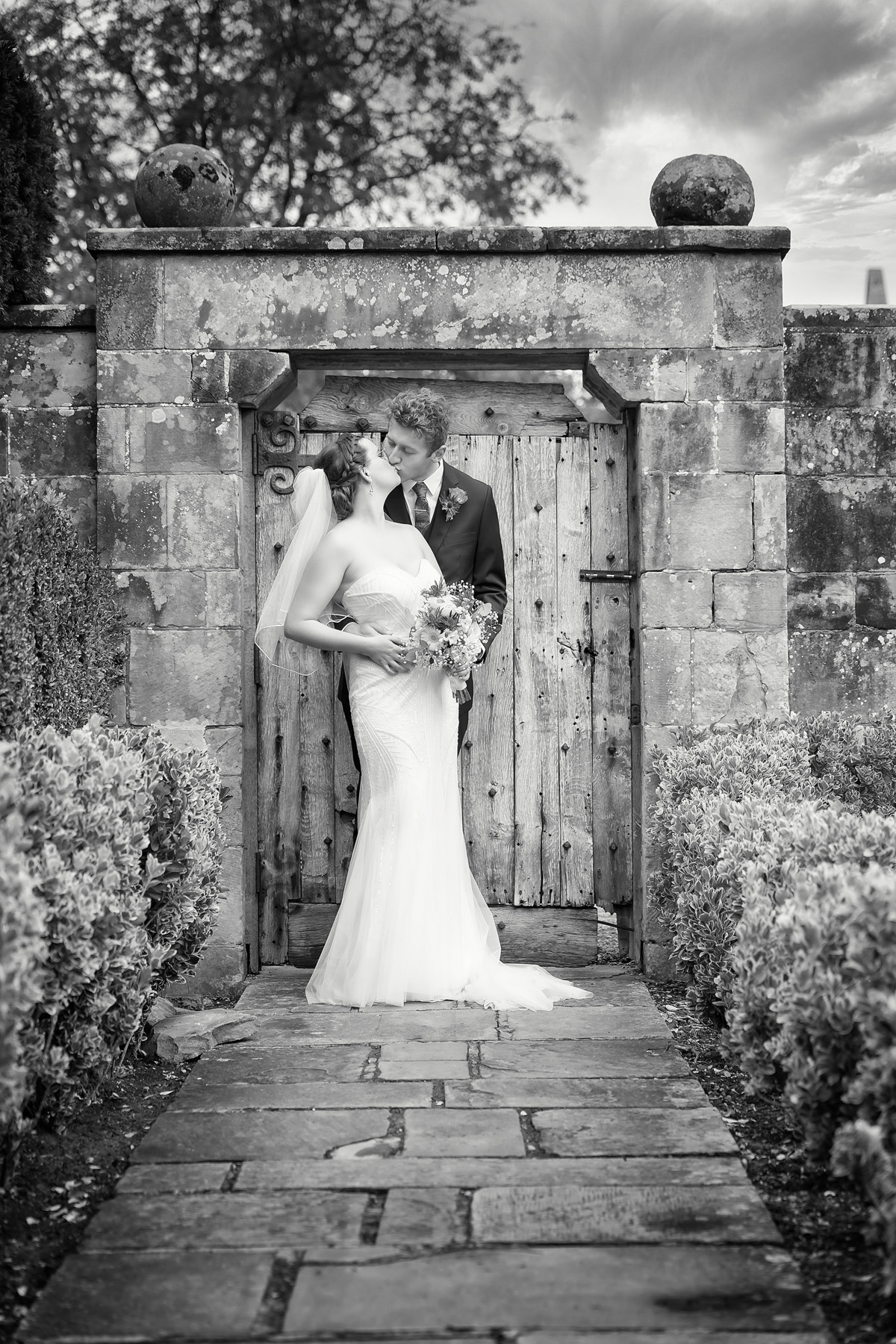 Bride and Groom romantic black and white wedding portrait in front of coombe abbey's old rustic wood door & stone arch