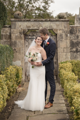 Fun natural wedding portrait photography, happily laughing couple in front of old wooden door and stone archway at Coombe Abbey