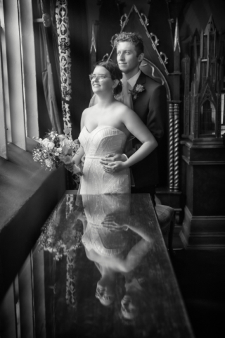 Beautifully lit natural light wedding portrait of couple in front of old window in the strawberry corridor at Coombe abbey