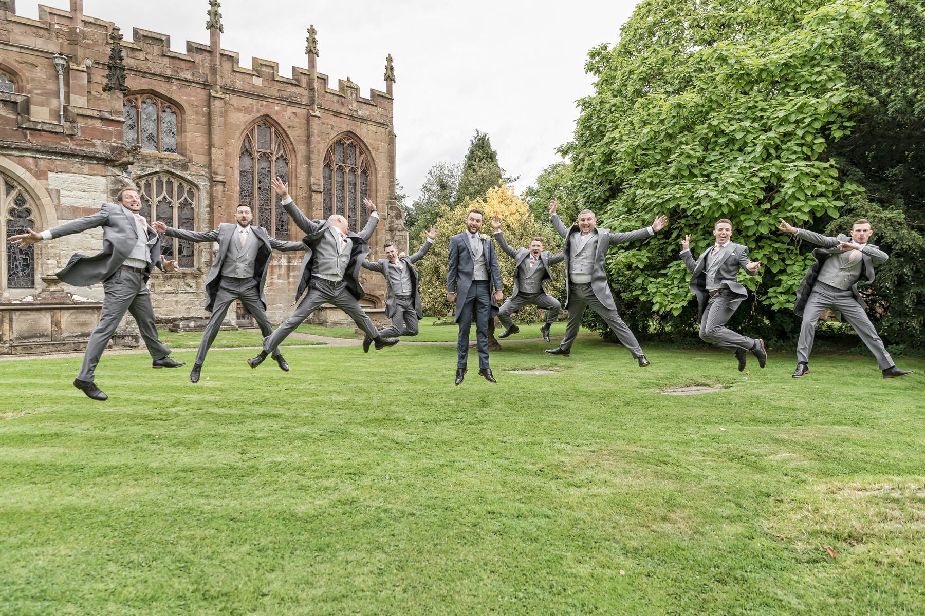 Groom & Grooms-men fun star jump photo before wedding at Knowle Church