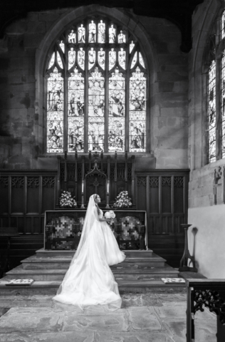 Beautiful black & white bridal portrait in front of stain glass window at Knowle Church