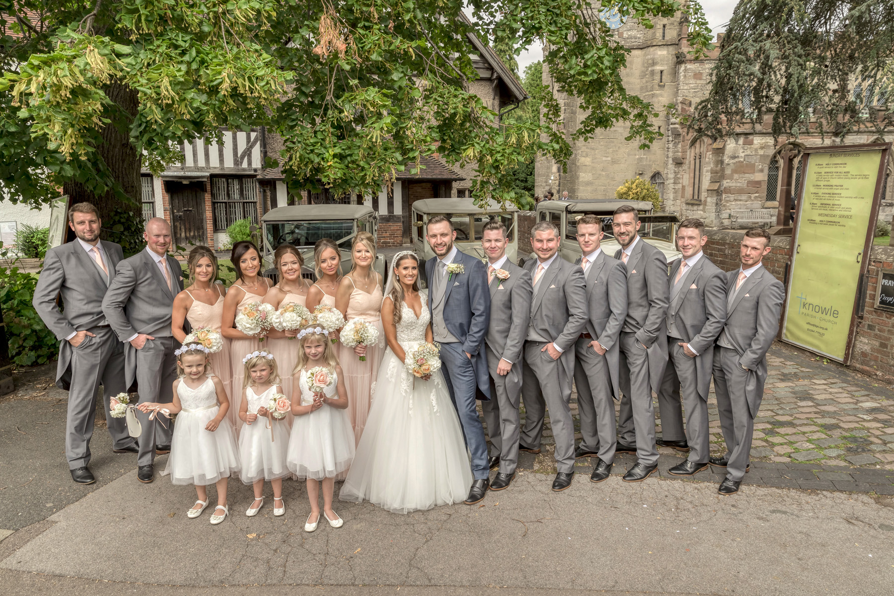 Bridal party in front of vintage cars at Knowle Church
