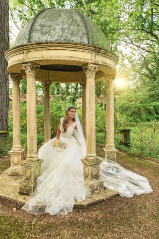 Moxhall wedding photography; Beautiful sunset photo with bride sitting under stone domed gazebo