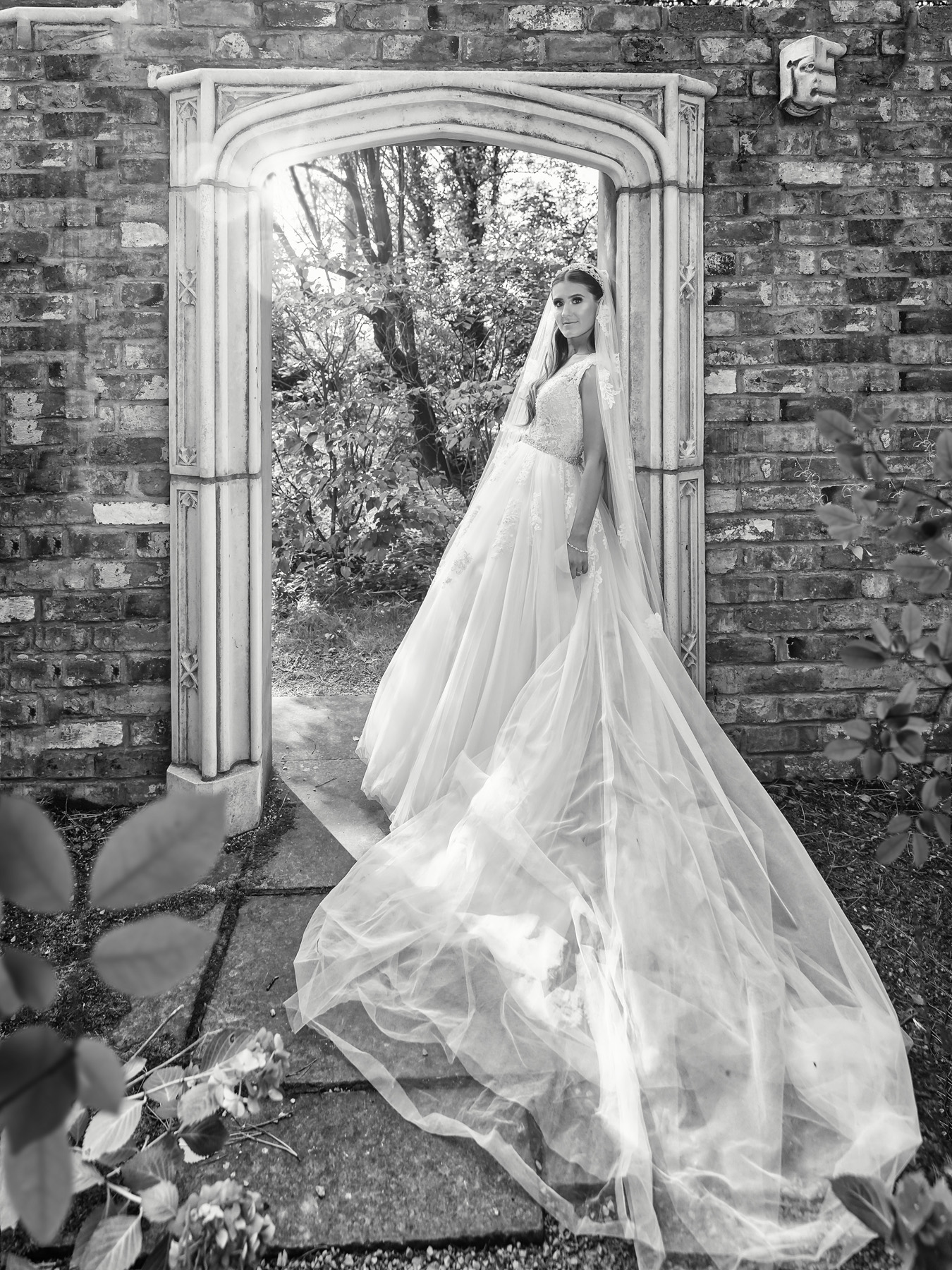 Classic black and white portrait of bride leaning against stone arch at sunset at Moxhall wedding