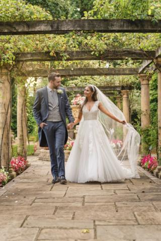 Bride & groom walking hand in hand under garden gazebo at Moxhall hall