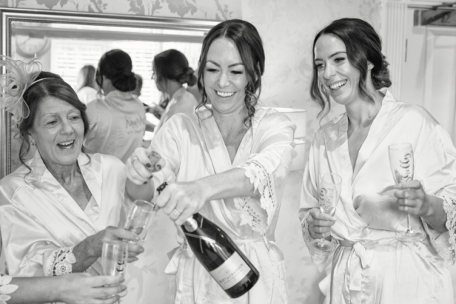 bridesmaids & mom opening champagne at Warwick house