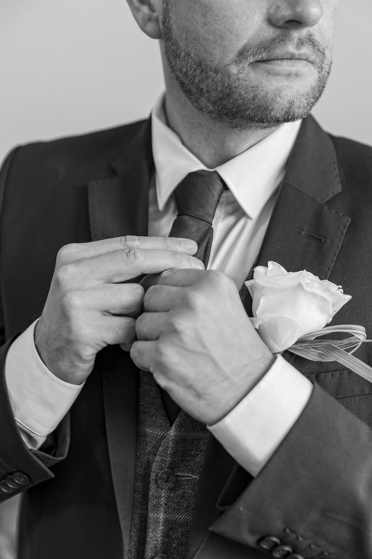 Groom doing his tie up before wedding at Warwick house