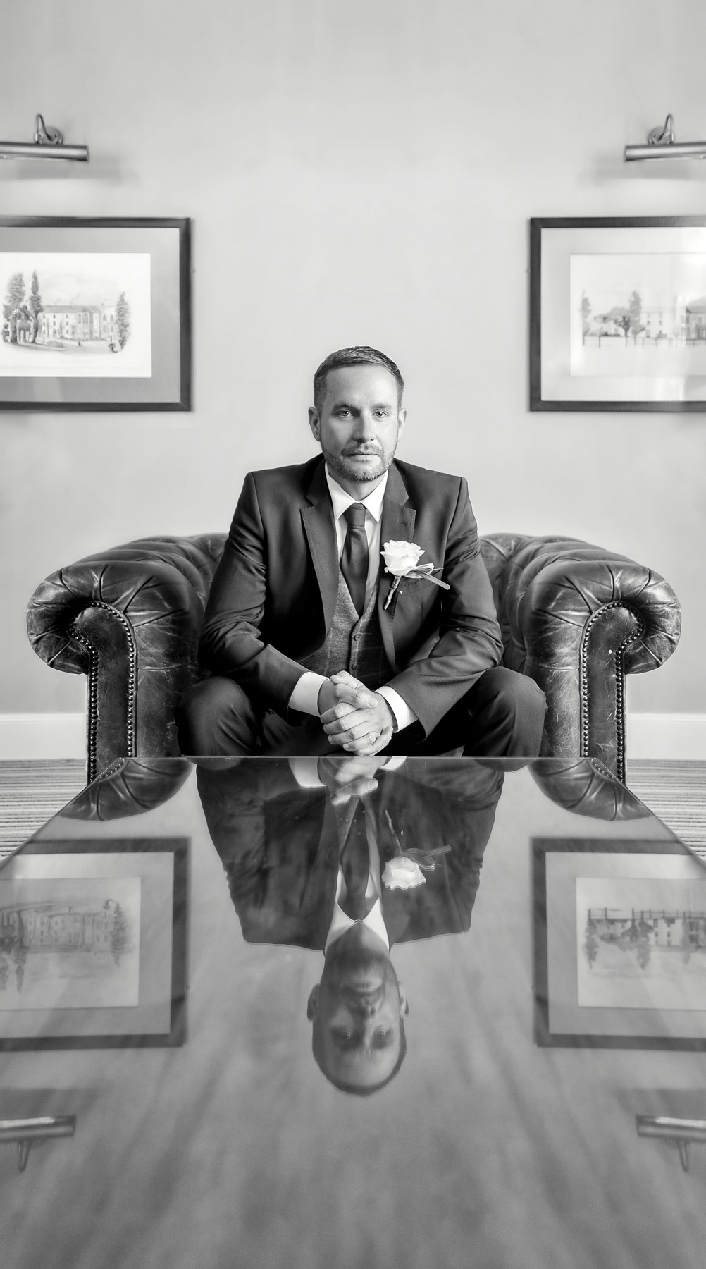 Classic black & white portrait of groom sitting. Wedding at Warwick house