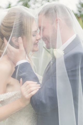 romantic portrait of bride and groom through veil - at Warwick house