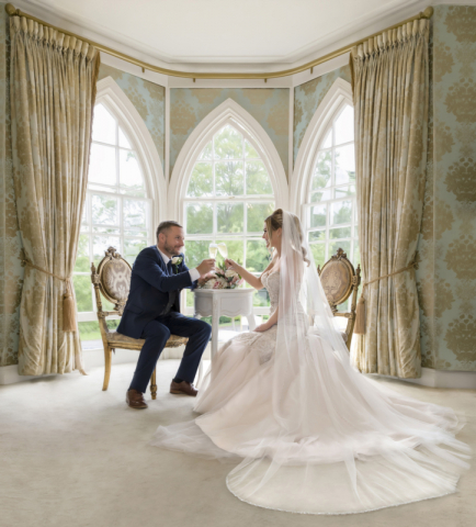 Bride & groom portrait. Sitting having a romantic drink together in bridal suit at Warwick house