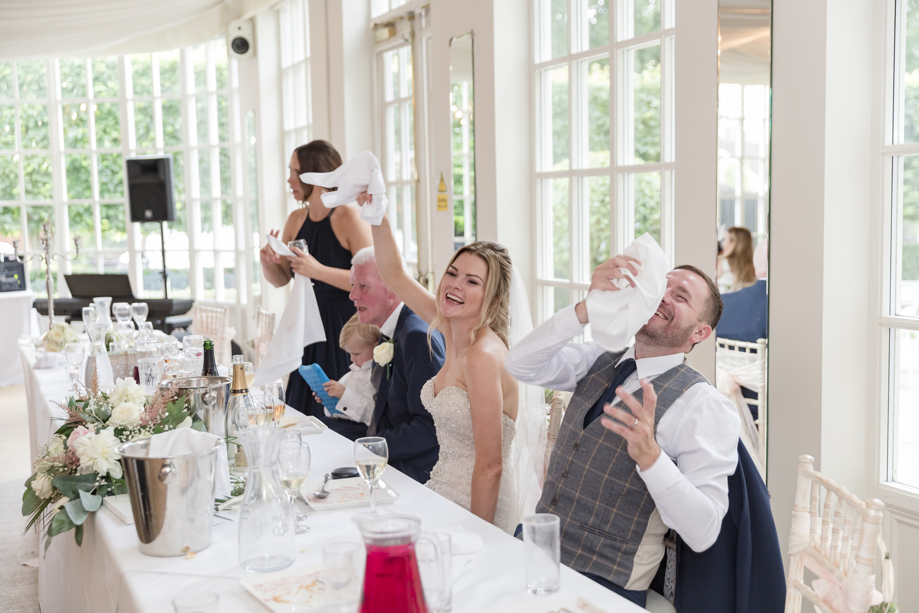 Bride & groom laughing during fun entertainment during meal at Warwick house
