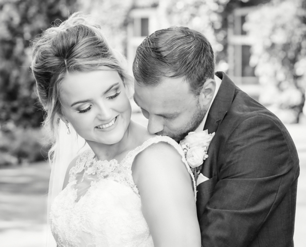 Groom kissing brides shoulder ; Romantic bride and groom black and white wedding portrait taken at their Ardencote wedding