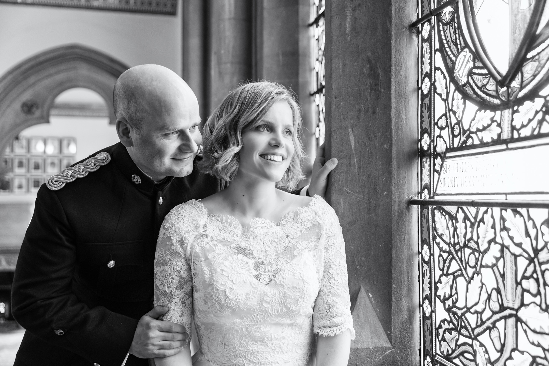 Black & white portrait of Bride & Groom looking out of stain glass window at Walton hall