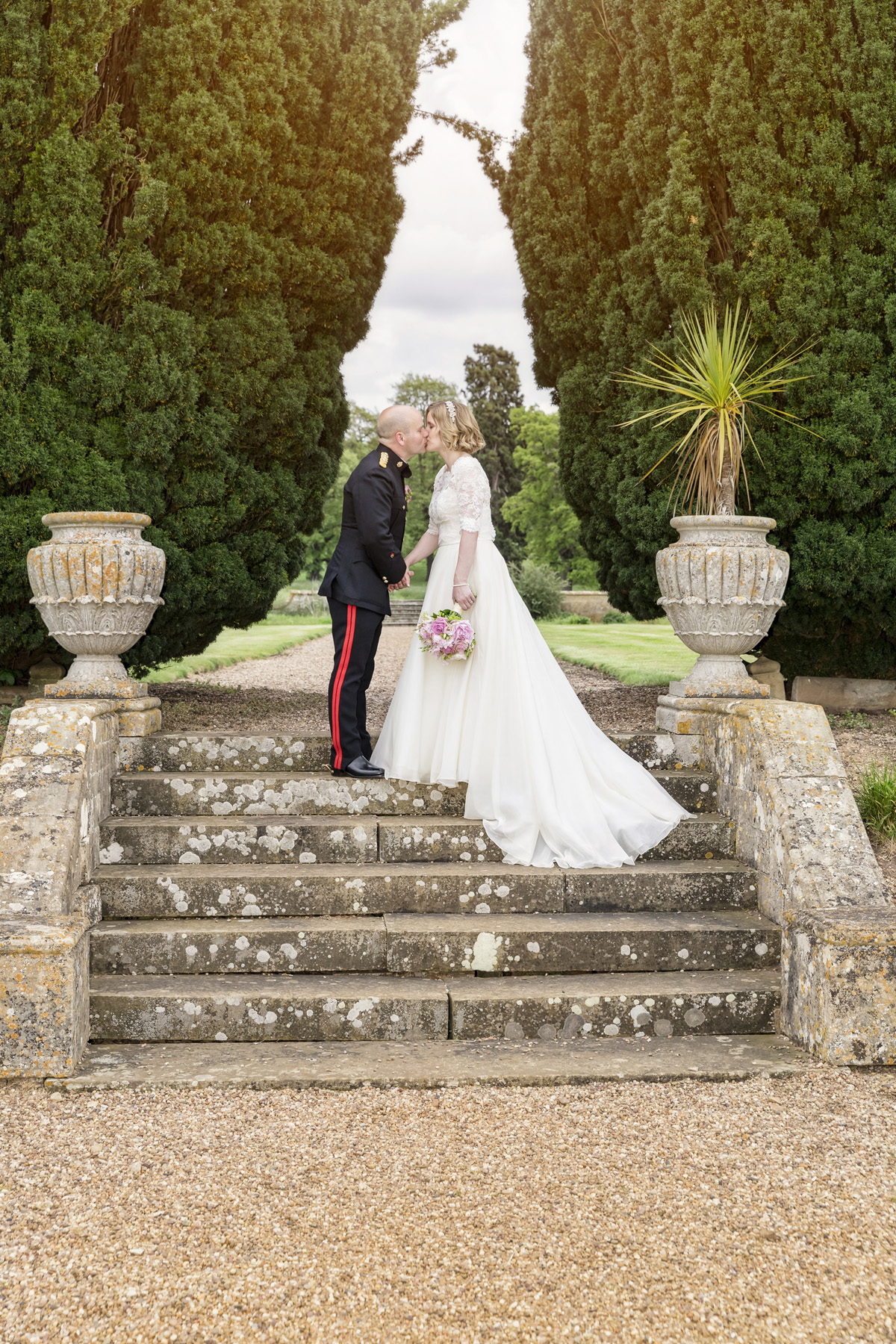 Bride & groom kissing on top of outdoor stone stairs at Walton hall