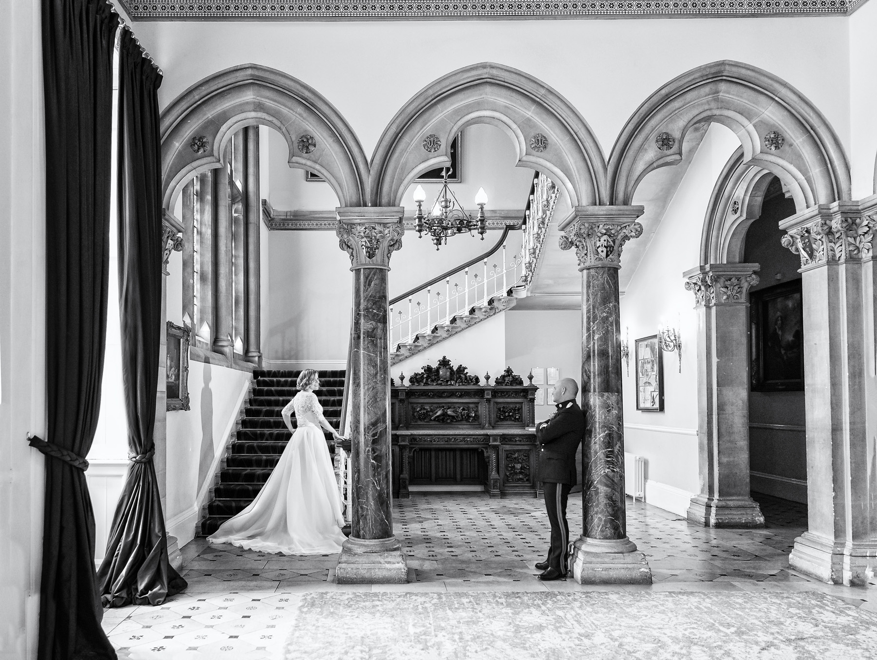 Black & white classic portrait of Bride & groom in marble arched reception entrance at Walton hall