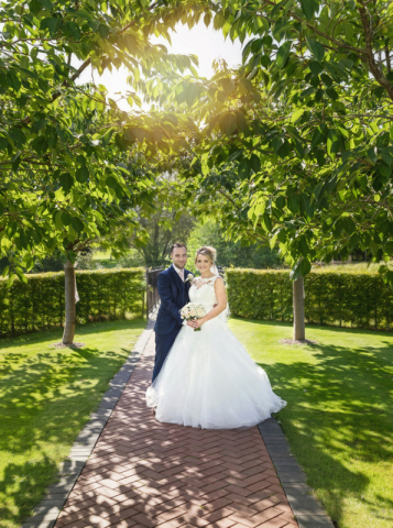 Bride and groom in an archway of trees at Ardencote Manor hotel