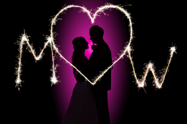 Sparkler wedding photography; bride and groom night silhouette portrait  on their wedding day with their initials written with sparklers