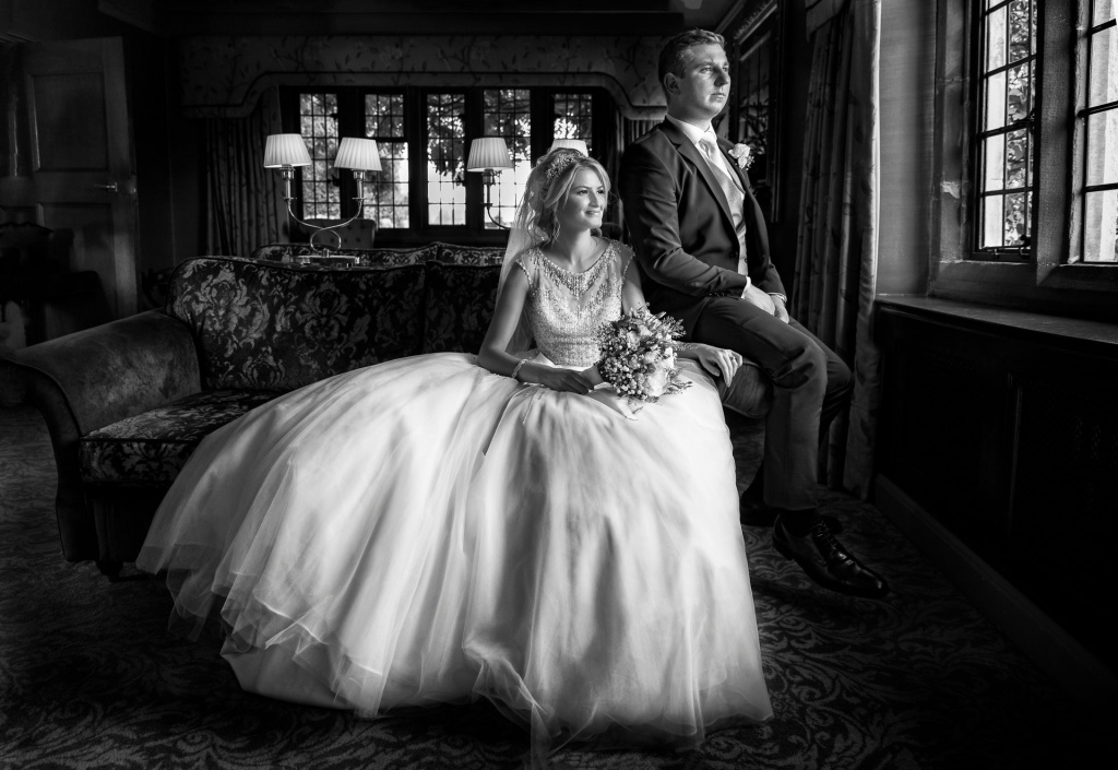 Black and white image of bride and groom sitting in the drawing room at Mallory court