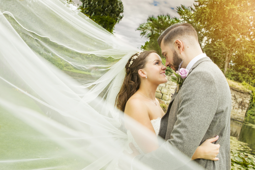 bride and groom looking lovingly at each other by the pretty river avon