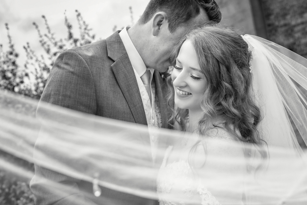 black & white image of bride & groom with bridal veil sweeping infront of them