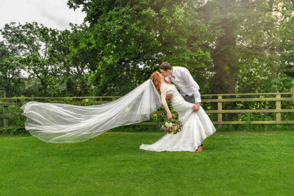 Beride & grrom kissing as he dips her back. Her veil floating down behind her