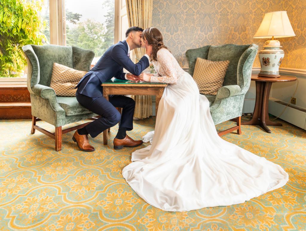 Bride & Groom kissing Bride & groom sitting in armchairs sharing a romantic kiss at Ettington Park Hotel