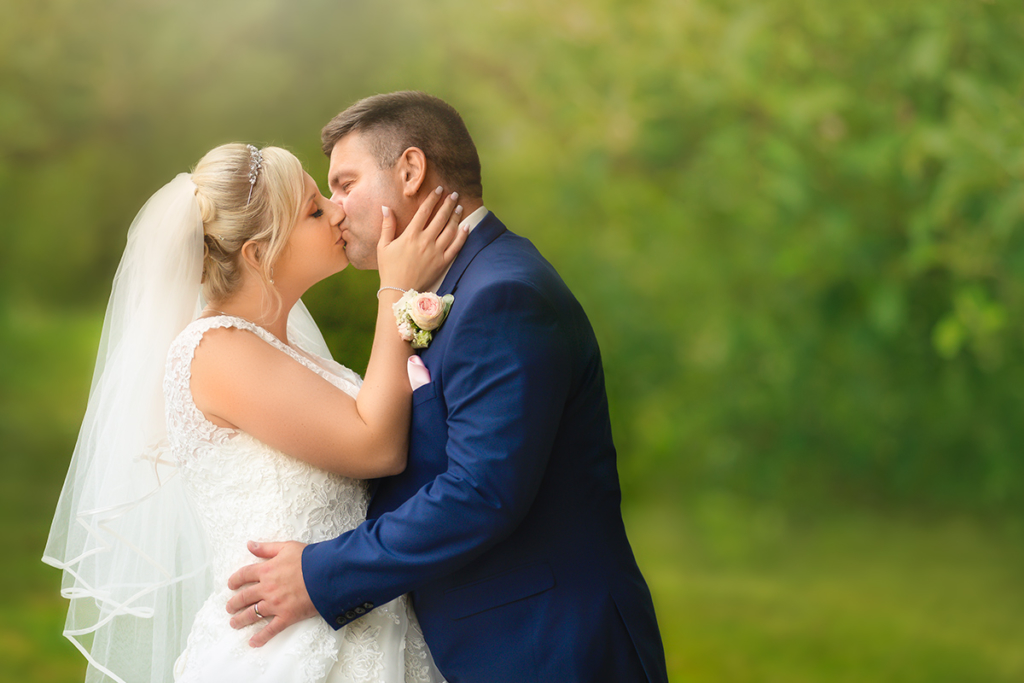 romantic photo of bride wearing a bridal veil kissing her husband